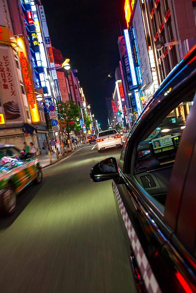 Motion blurred view from taxi of street and neon advertising signs at night in Shinjuku District, Tokyo, Japan