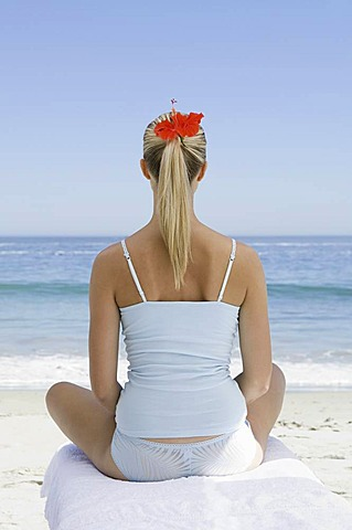 The beach. A young woman seated on a towel on the sand in a relaxed pose, looking out to sea, Cape Town, South Africa