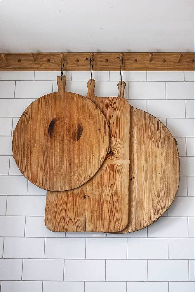 Close up of small selection of wooden cutting boards hanging on tiled white wall