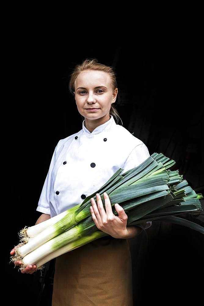 Woman wearing chef's jacket standing indoors, holding bunch of leeks, looking at camera
