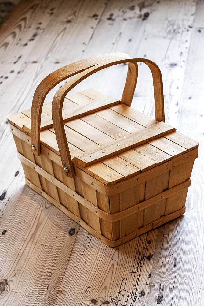 High angle close up of wooden picnic basket on wooden floor