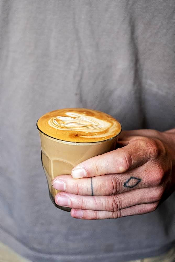 Close up of person with tattooed finger holding glass of cafe latte