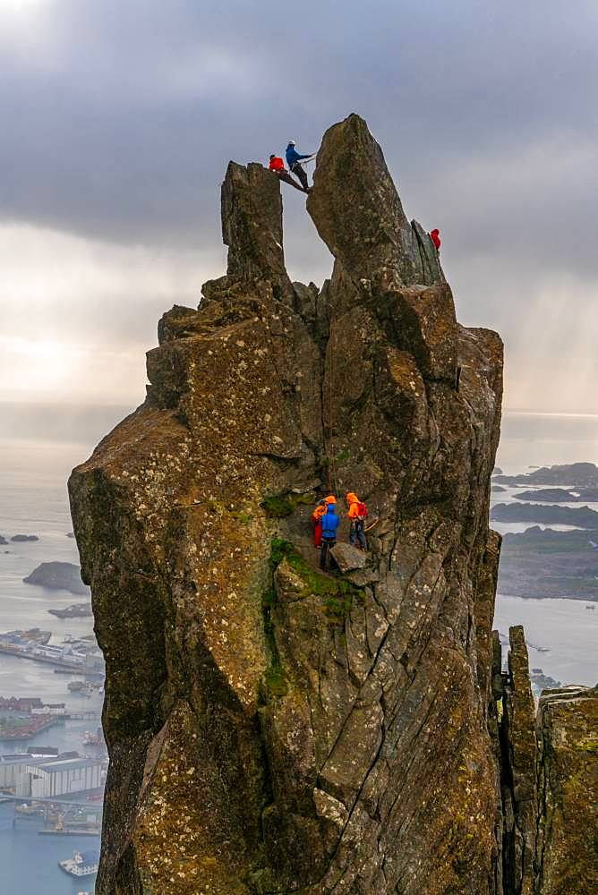 A group of people climbing on the Svolvaer Goat, 150-metre (490 ft), a jagged pinnacle high above the landscape of the Lofoten, Austvagoy, Lofoten Islands, Norway