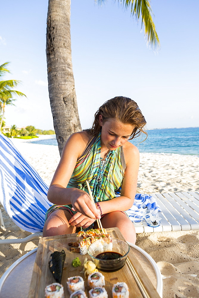 A teenage girl sitting in a beach chair, Grand Cayman, Cayman Islands