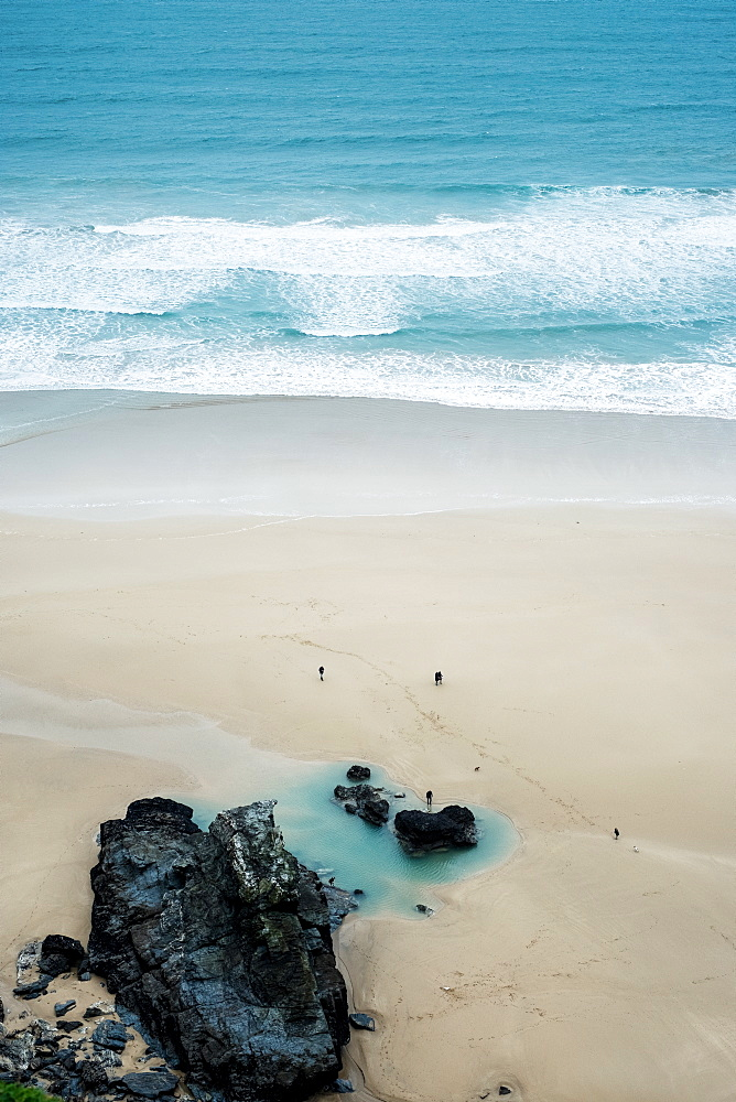 High angle view of ocean waves and rocks on a sandy beach