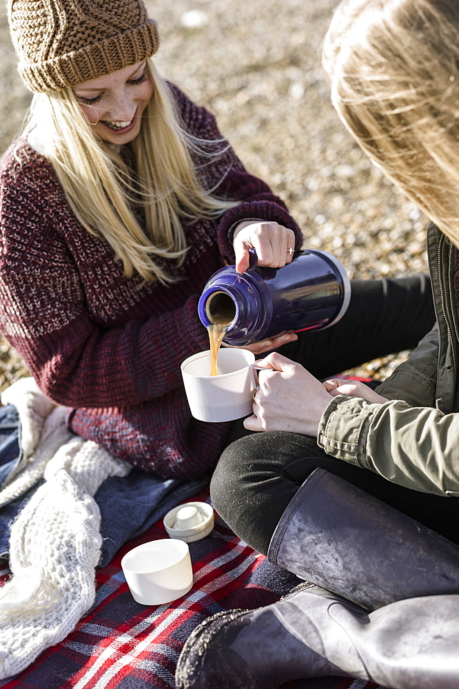 Two girls having a winter picnic on the beach, Hampshire, England