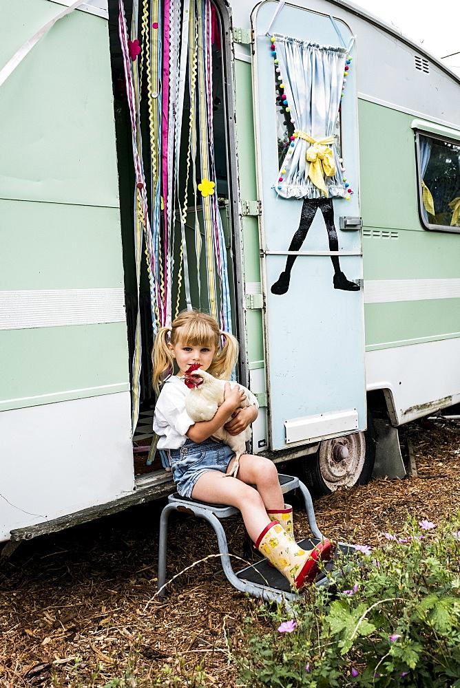 Blond girl holding white chicken sitting outside a caravan - 1174-7153