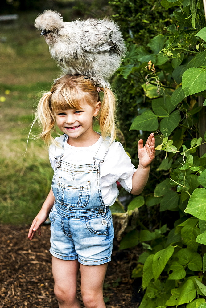 Smiling blond girl standing in a garden, with a fluffy grey chicken on her head