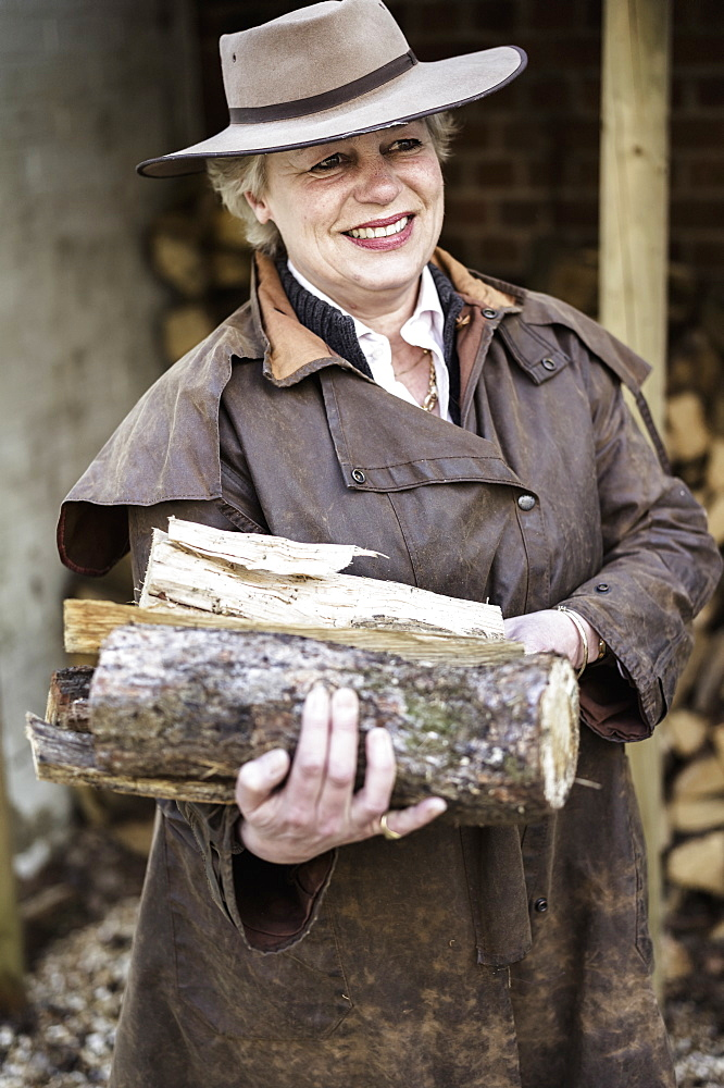 A woman carrying split logs for firewood from a large log store, Ringwood, Hampshire, England