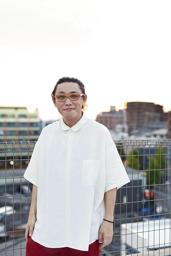 Young Japanese man standing on a rooftop in an urban setting, looking at camera, Fukuoka, Kyushu, Japan