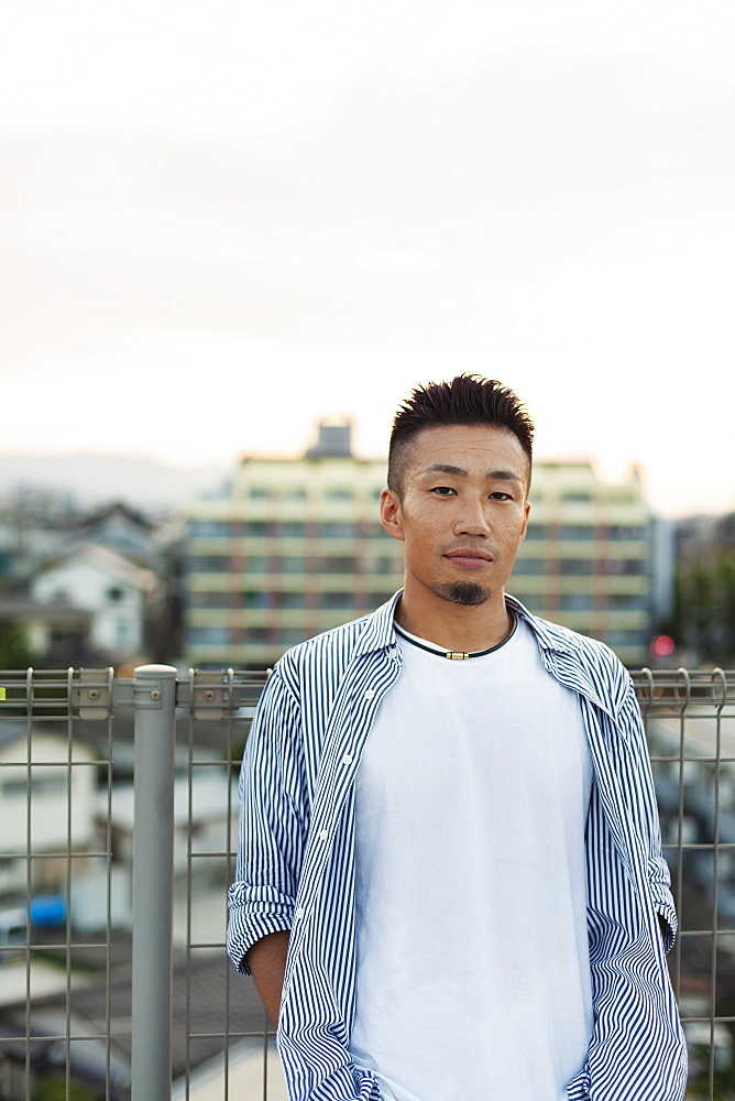 Young Japanese man standing on a rooftop in an urban setting, looking at camera, Fukuoka, Kyushu, Japan