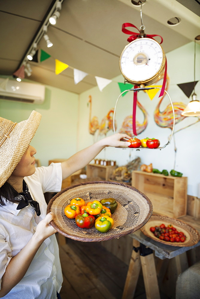 Japanese woman wearing hat working in a farm shop, weighing fresh vegetables, Kyushu, Japan