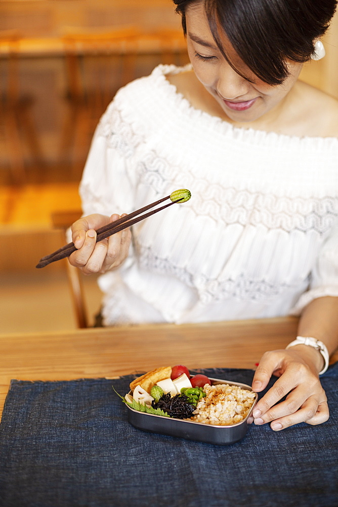 Japanese women eating with chopsticks in a vegetarian cafe, Kyushu, Japan