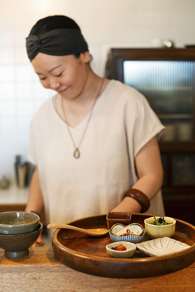 Japanese woman preparing fresh vegetables in a vegetarian cafe, Kyushu, Japan