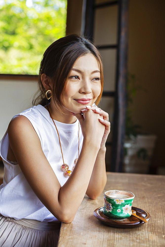 Smiling Japanese woman sitting at table in Japanese restaurant, Kyushu, Japan