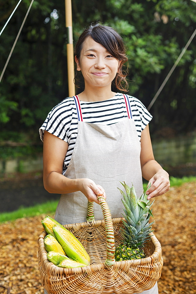 Smiling Japanese woman wearing apron standing outdoors, holding basket with fresh vegetables, looking at camera, Kyushu, Japan