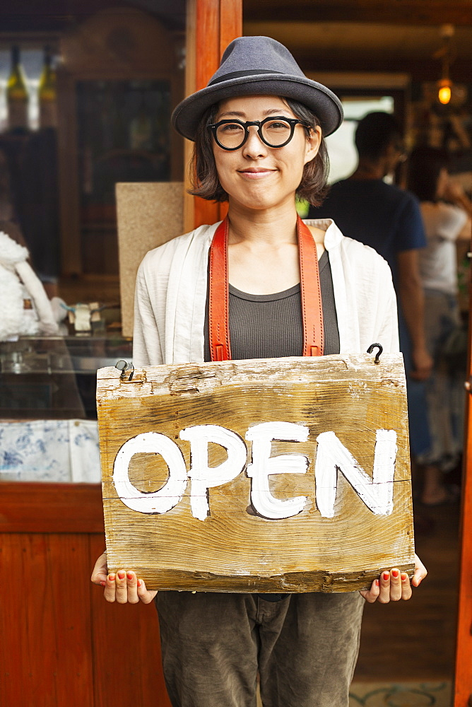 Japanese woman wearing hat and glasses standing in front of a leather shop, holding Open sign, Kyushu, Japan
