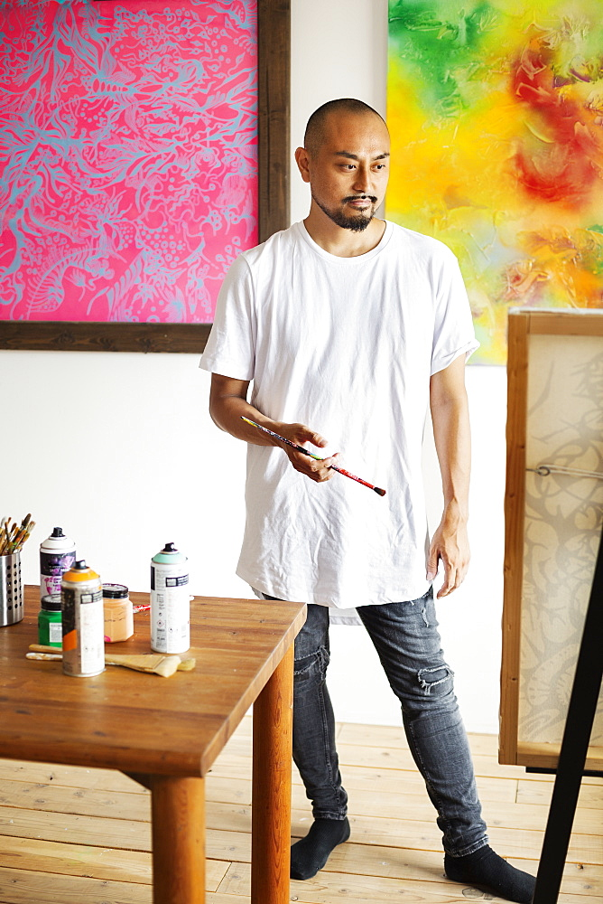 Japanese man standing in art gallery, holding paintbrush, looking at artwork on easel, Kyushu, Japan