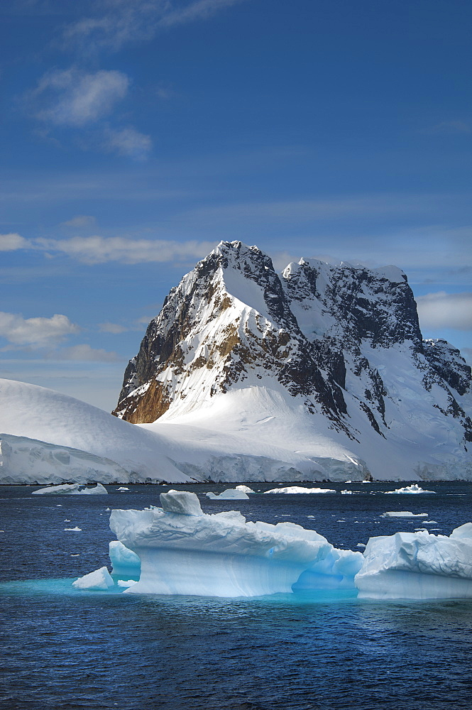 Icebergs floating in the water off the rocky shore of Antarctica, Antarctic mountains, Antarctica