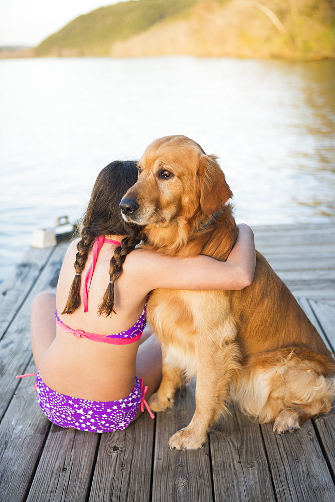 A young girl and a golden retriever dog sitting on a jetty, Austin, Texas, USA