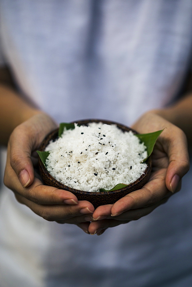 High angle close up of hand holding coconut flesh and black sesame seeds used as a body scrub, Thailand