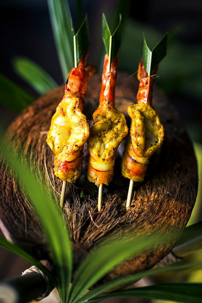 High angle close up of charcoal-grilled prawn satay on a coconut shell, Thailand