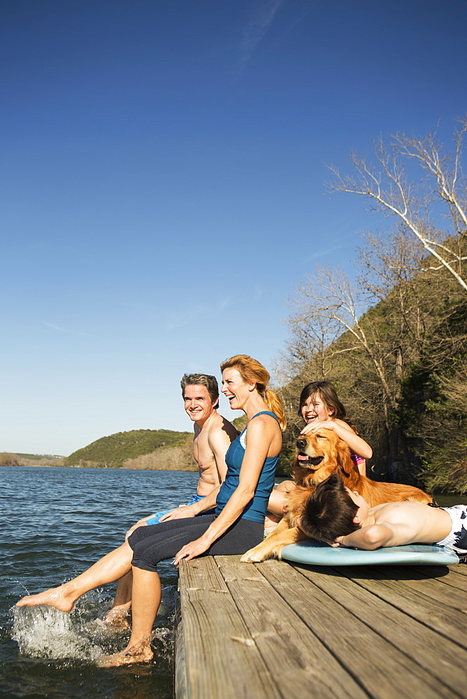 A family and their retriever dog on a jetty by a lake, Austin, Texas, USA