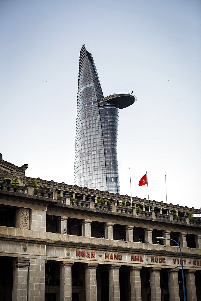 Facade of historic stone building with contemporary skyscraper in the background, Vietnam