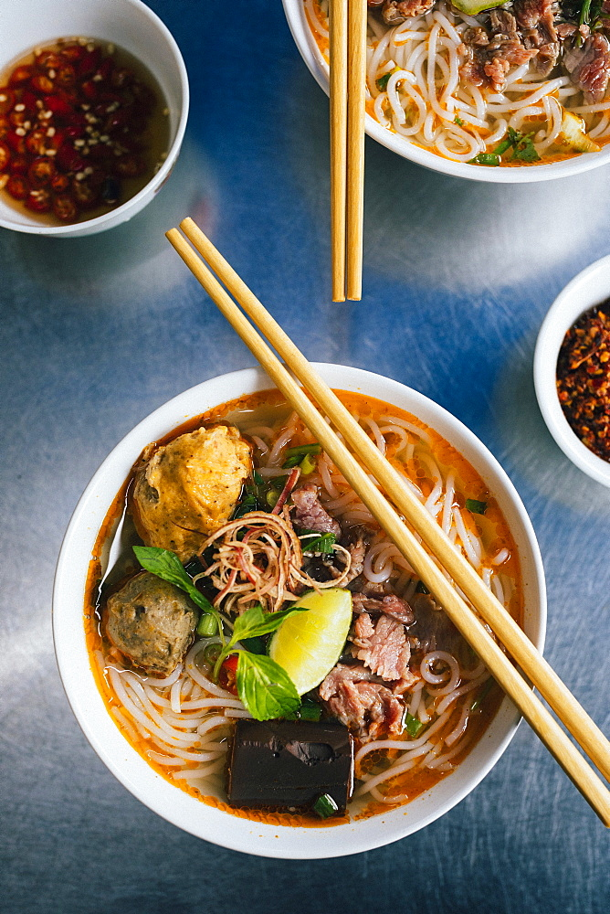 High angle close up of bowl of Bun Bo Hue with beef, crab balls, blood sausage and herbs, Vietnam