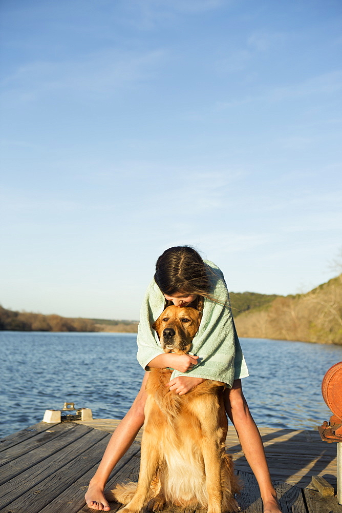 A girl cuddling a golden retriever dog, Austin, Texas, USA