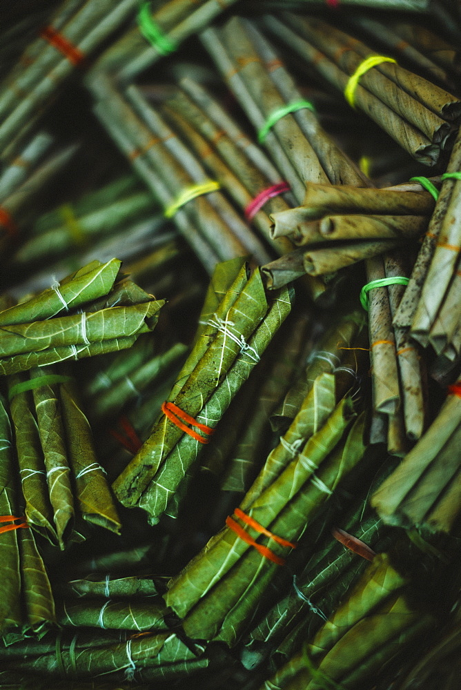 High angle close up bundles of beedi cigarettes, tobacco wrapped in green leaves and tied with a string, India