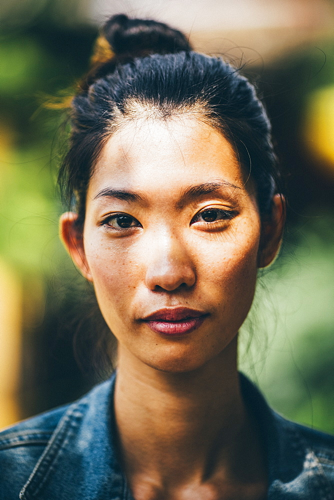 Portrait of a young woman with black hair tied in a top knot, looking at camera, Vietnam