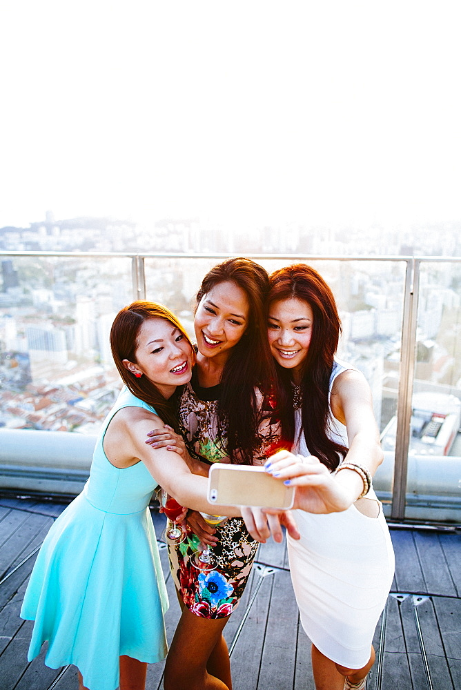 Three women standing on a rooftop in Singapore, taking selfie with cell phone, Singapore