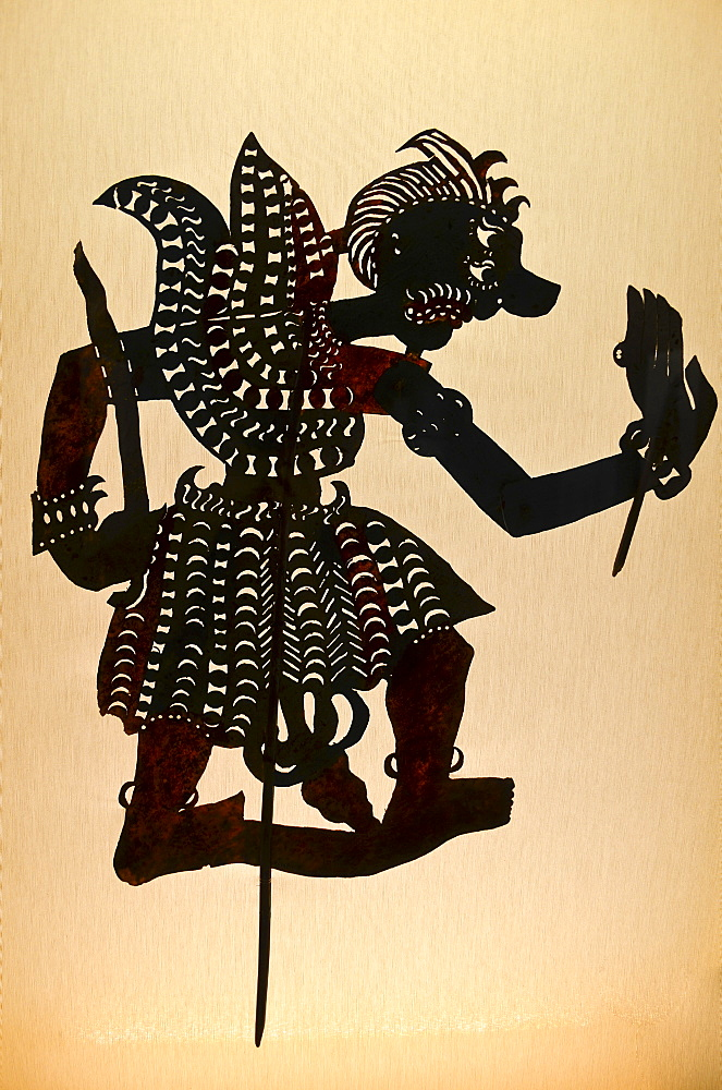 Silhouette of a shadow puppet, a jointed shape of a warrior, a wayang puppet from Indonesian culture, Indonesia