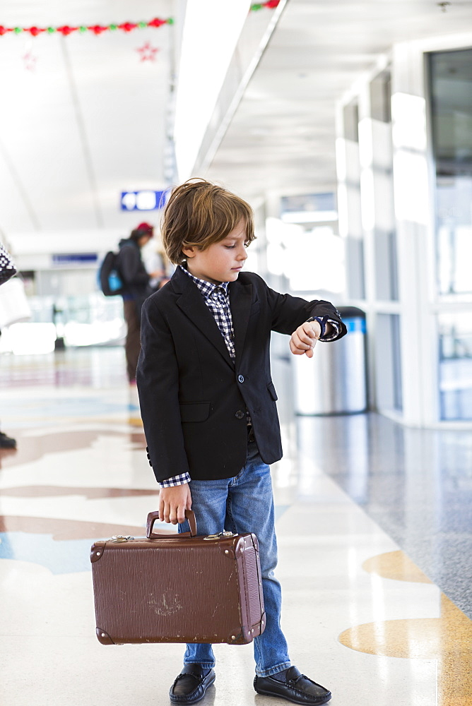 A young boy looking at his watch in airport, St Simon's Island, Georgia, United States