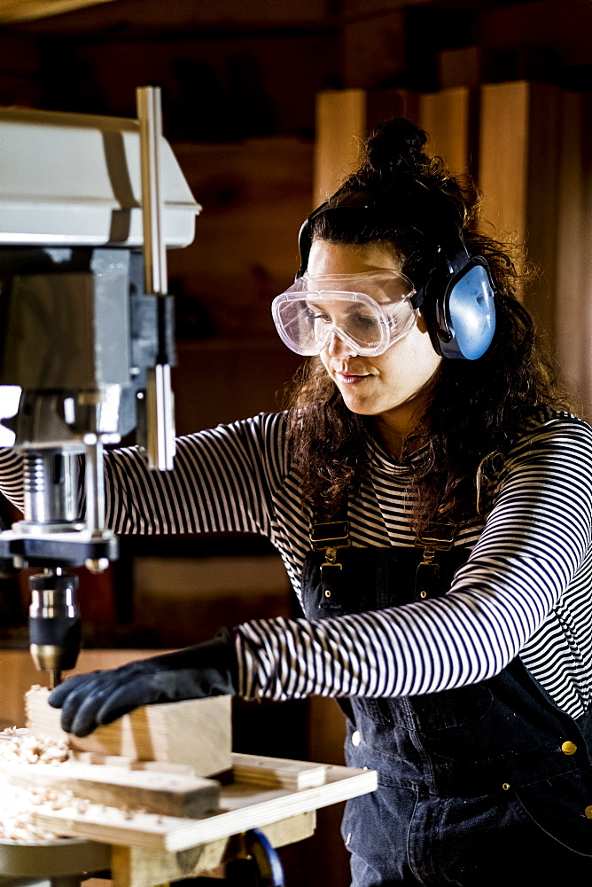 Woman with long brown hair wearing dungarees, safety glasses and ear protectors standing in wood workshop, using electric drill, Oxfordshire, United Kingdom