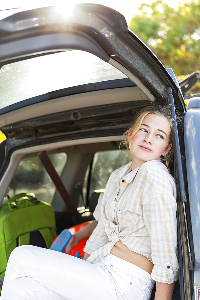 A teenage girl in the back of an SUV with luggage, United States - 1174-7921