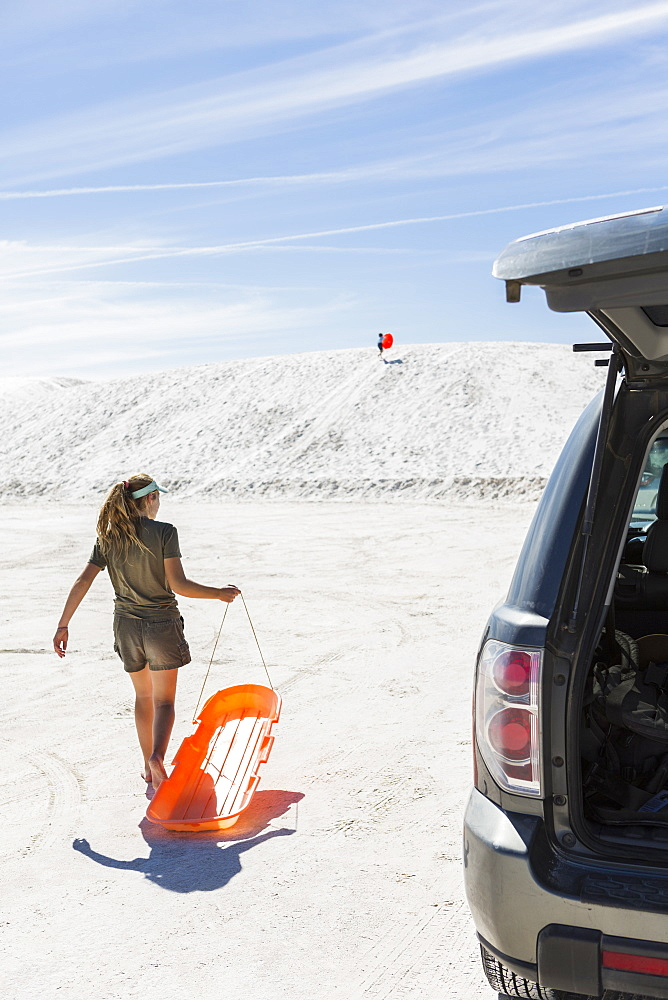 Teenage girl with a sled on white sand dunes, White Sands National Monument, New Mexico, United States - 1174-7962