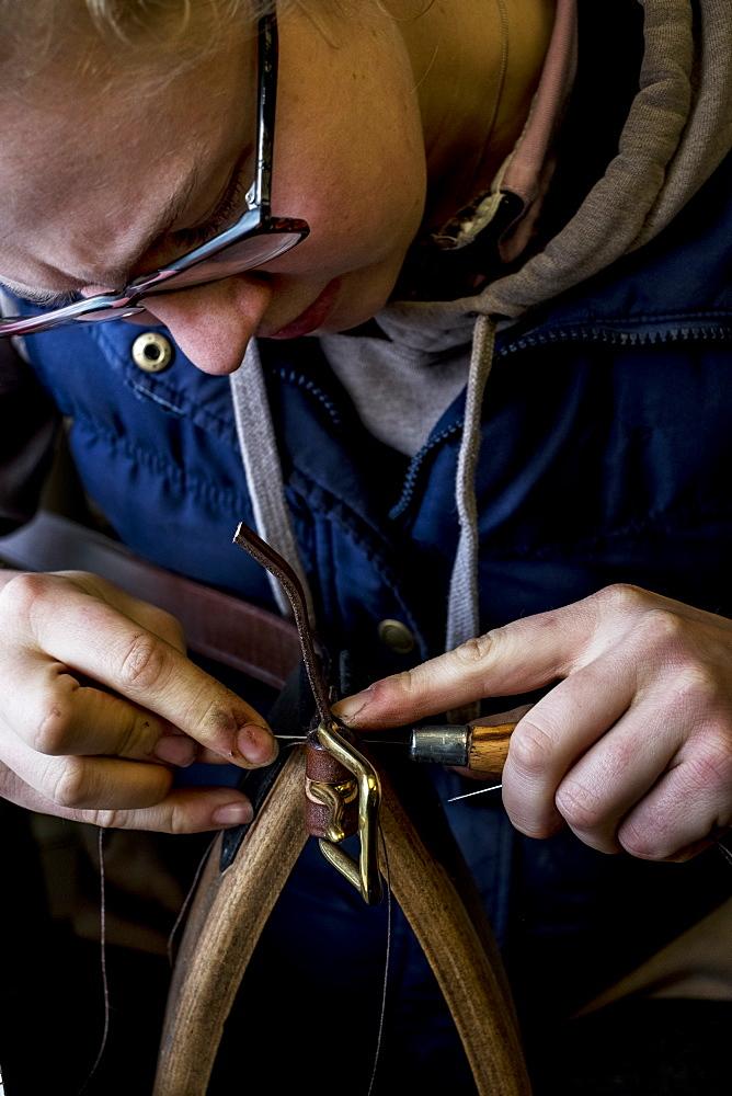 Close up of female saddler standing in workshop, working on leather strap, Berkshire, United Kingdom