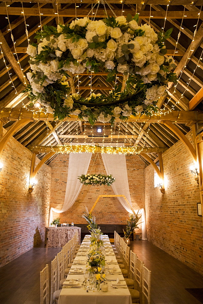 Long dining table with festive place settings for a naming ceremony in an historic barn
