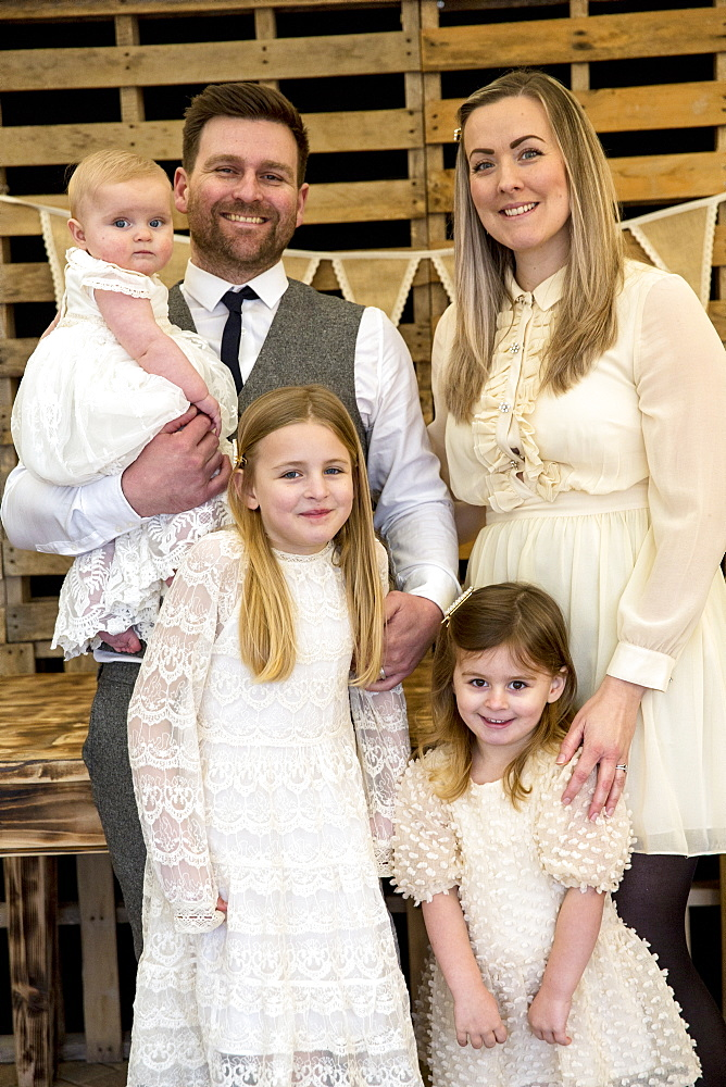 Portrait of smiling parents with their three young daughters during naming ceremony in an historic barn