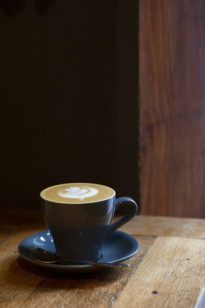 Close up of cup of Cappuccino on a rustic wooden table in a cafe