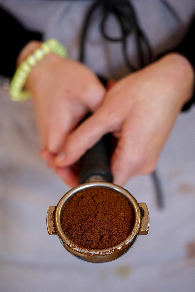 High angle close up of barista holding espresso machine portafilter