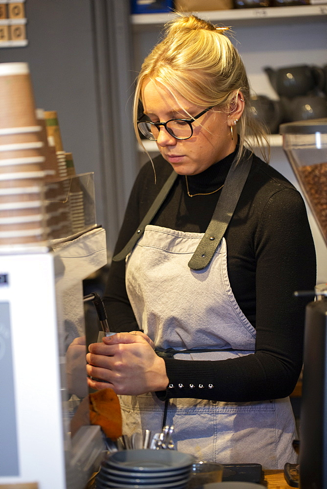 Blond woman wearing glasses and apron standing at espresso machine in a cafe, frothing milk
