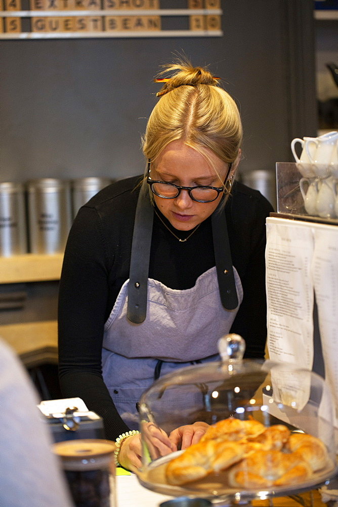 Blond woman wearing glasses and apron standing at espresso machine in a cafe, writing down a note