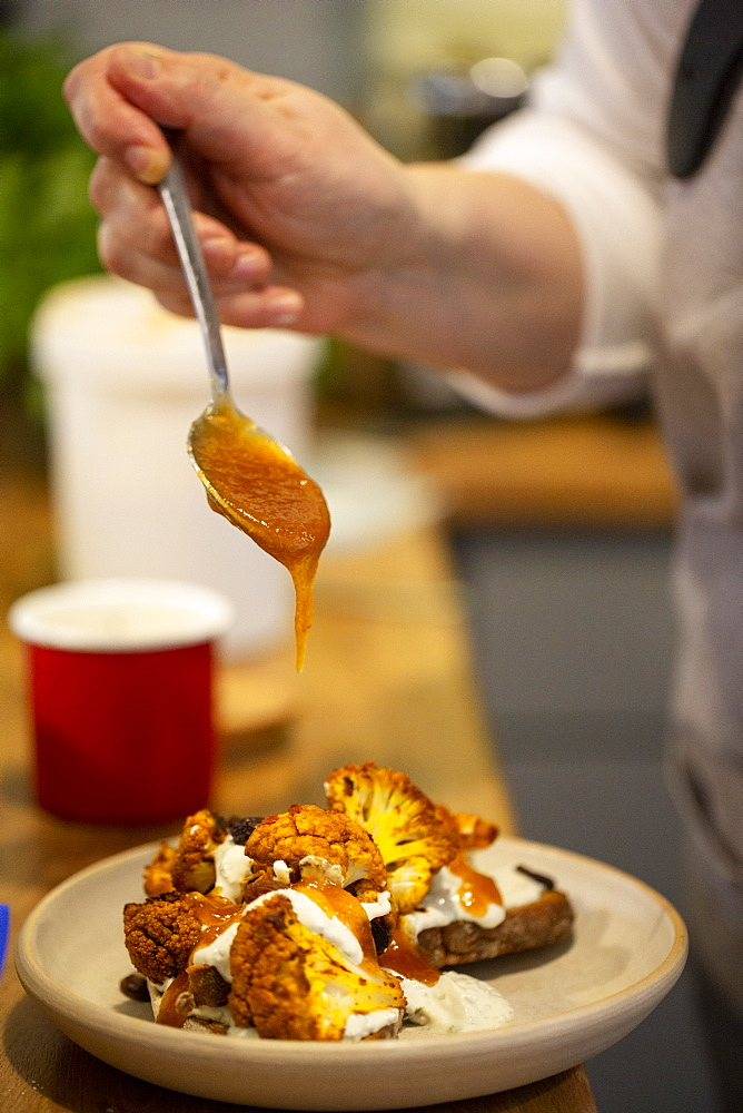 Close up of person drizzling mango chutney onto roasted cauliflower with yoghurt and sesame seeds on toasted sourdough bread in a cafe