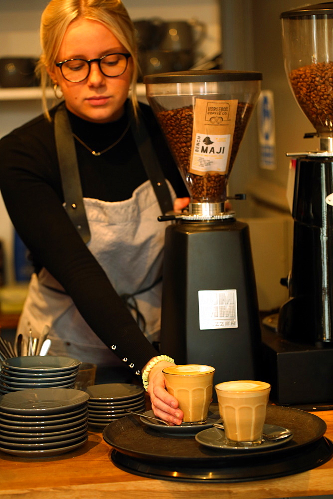 Blond woman wearing glasses and apron standing at counter in a cafe, placing two cafe lattes on a tray
