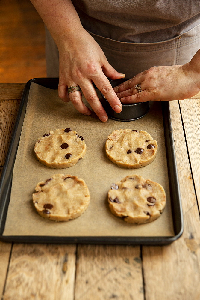 High angle close up of person standing at wooden table, baking chocolate chip cookies