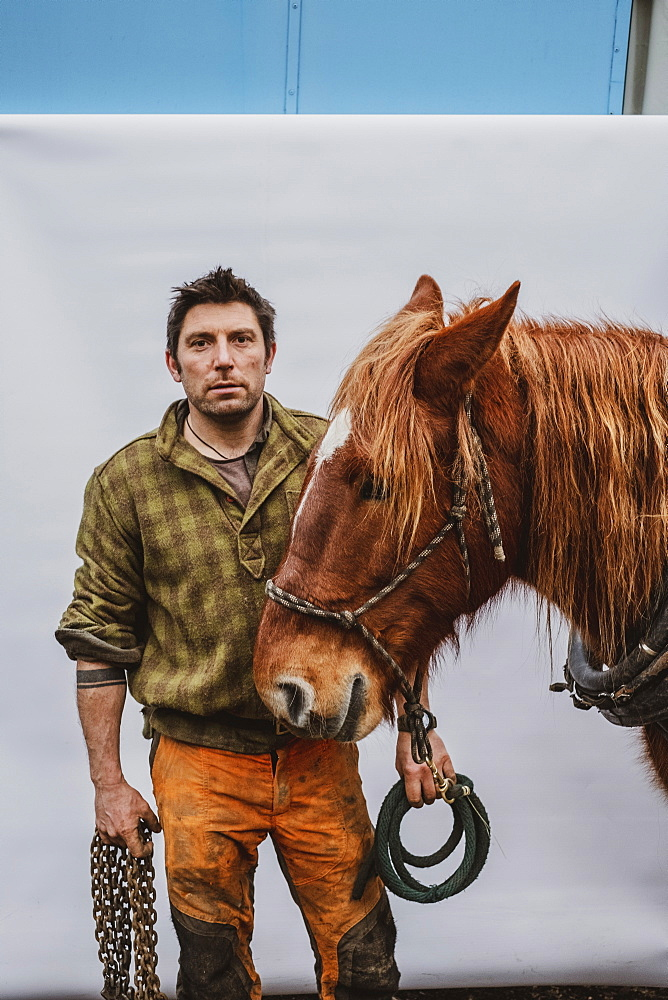 Portrait of a logger with one of his work horses, Devon, United Kingdom