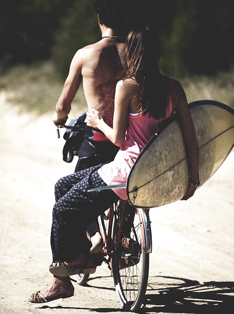Rear view of man and woman on a bicycle, woman sitting on rack, holding a surfboard